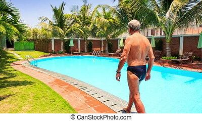 Bearded Old Man Walks along Swimming Pool - european...