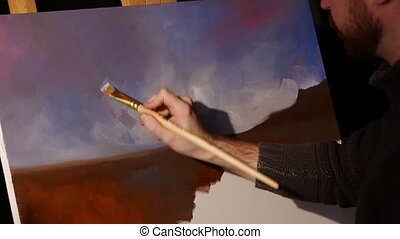 Bearded painter goes on drawing a new painting with sky and ground by oil paints on easel holding the palette in his hand, black background, back light, slow motion