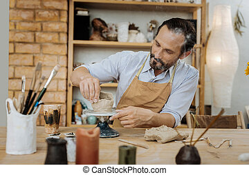 Bearded potter feeling happy while working in his workshop