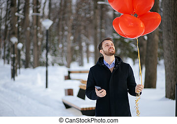 bearded romantic man with red air ballons at winter park