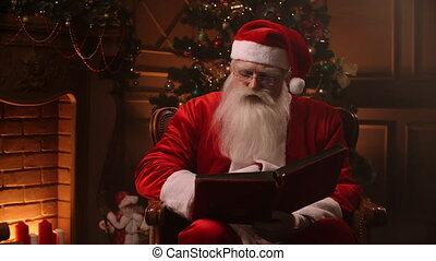 Bearded senior man in santa clause outfit flipping through pages of book with red cover in thematically decorated room - christmas spirit concept close up