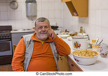 Bearded senior man sitting on a chair in kitchen