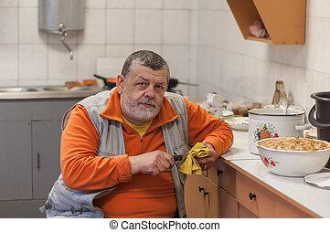 Bearded senior man working in kitchen