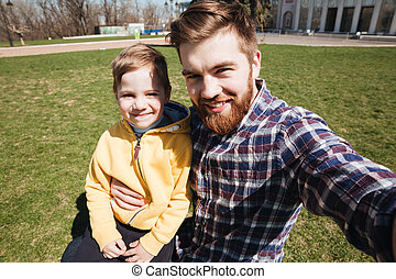 Bearded smiling father outdoors with his little son