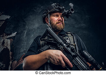 Bearded special forces soldier or private military contractor holding an assault rifle and observes the surroundings in night vision goggles.