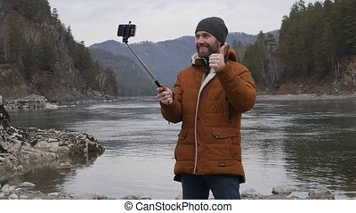 bearded tourist photographs himself on a mobile phone on the...