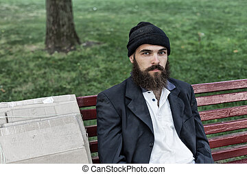Bearded vagrant sitting on the bench