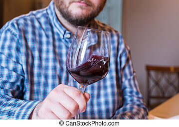 Bearded White Man Swirling Red Wine in a Glass