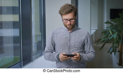 Bearded worker of the institute plays in the lobby on your smartphone.