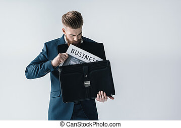 Bearded young businessman putting newspaper in briefcase