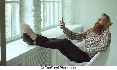 Bearded young hipster businessman talking video chat on smartphone while sitting in offce chair with his legs on windowsill