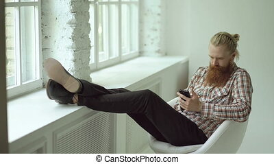 Bearded young hipster man sms texting using smartphone while sitting in offce chair with his legs on windowsill