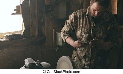 Bearded young man blacksmith manually polish metal knife on...