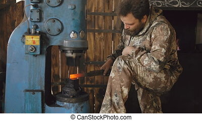 Bearded young man blacksmith using hydraulic press for steel...