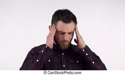 Bearded young man suffering from terrible headache, rubbing...