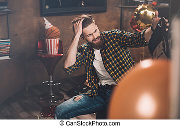 Bearded young man with headache holding black bra after party