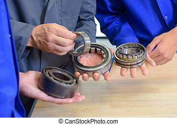 Bearings held in the hands of three people