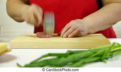 Beat The Pork Chop - Mature woman preparing pork chop,...