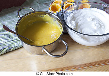 Beaten egg in a glass bowl and cream in a metal pan.