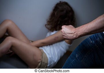 Beaten women on a floor with her torturer