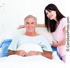 Beatiful female nurse adjusting pillows for a senior patient