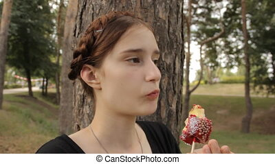 Beatiful girl eats candy apple. Zoom in and out.