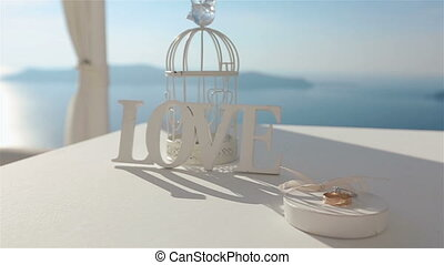 Beatiful wedding tent aisle at coast with wedding rings on the table and sea with mountains background