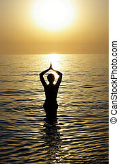 Young beatiful woman meditating in a sea
