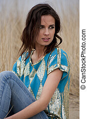Beatiful woman wearing blue and gold shirt with jeans