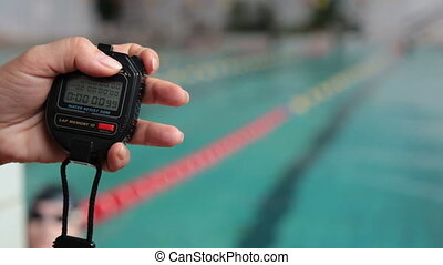 hand of coach with a stopwatch during competitions in the swimming pool