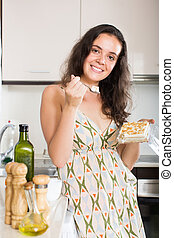 Beaty woman eating sweet dessert and smiling in home kitchen