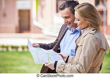 beau, élégant, mi, âge, couple, debout, outdoors., vue côté, de, femme souriante, tenue, carte, et, regarder, carte