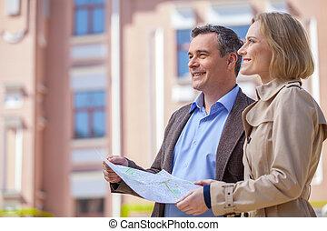 beau, élégant, mi, âge, couple, debout, outdoors., vue côté, de, femme souriante, tenue, carte, et, regarder