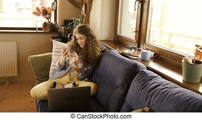 beau, adolescent, smartphone, texting, séance, ordinateur portable, suivant, divan, girl, elle.