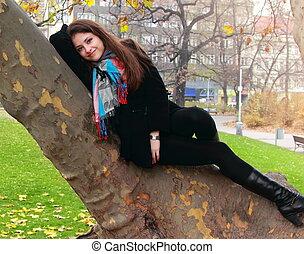 beau, automne, femme relâche, arbre, jaune, regarder, arrière-plan vert, coffre, mensonge