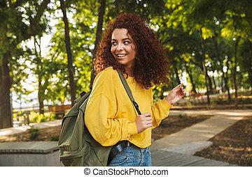 beau, backpack., marche, bouclé, nature, parc, jeune, étudiant, dehors, fille souriant
