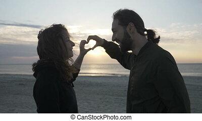 beau, coeur, lent, couple, mouvement, forme, coucher soleil, tenant mains, baisers, apprécier, plage, confection