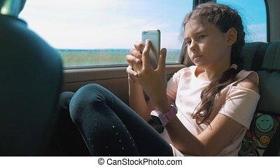 beau, concept, siège arrière, conversation, voiture., girl, ouvert, peu, voyage, long, sourire., numérique, percé, adolescent, carte, il, smartphone, séance, voyage, utilisation, gosse, voiture, mouvement