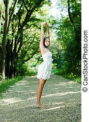 beau, debout, femme allonger, parc, jeune, haut, vert, mains, robe blanche