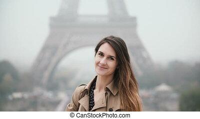 beau, debout, femme, eiffel, jeune, paris, france, sourire., appareil photo, portrait, tour, regarder