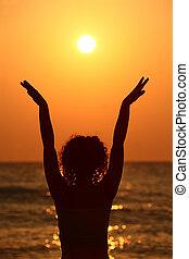 beau, debout, femme, elle, regarder, jeune, plage, augmentations, mains, coucher soleil