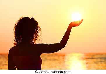 beau, debout, femme, regarder, soleil, jeune, plage, possession main, coucher soleil