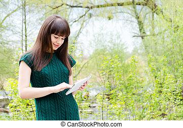 beau, debout, femme, tablette, verdure, dehors, jeune, charmer, ordinateur pc, magnifique, girl