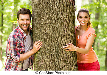 beau, debout, parc, couple, arbre, jeune regarder, quoique, sourire, aimer, nature., dehors