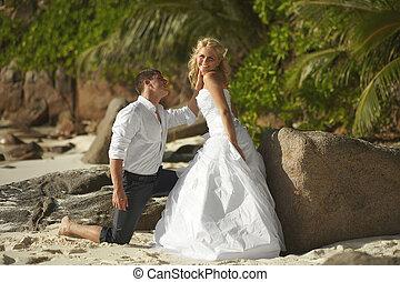 beau, debout, pieds nue, couple, jeune, baisers, stones., plage, coucher soleil