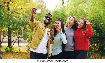 beau, debout, smartphone, appareil-photo., photo, selfie, filles, caucasien, jeunesse, parc, américain, poser, asiatique, étudiant, africaine, prendre, utilisation, concept.