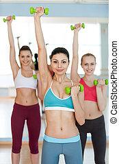 beau, dumbbells, poids, trois, jeune, appareil photo, training., sourire, vêtements de sport, exercisme, femmes
