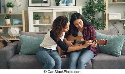beau, elle., quoique, asiatique, apprentissage, girl, habillement, désinvolte, elle, concept., jeune, passe-temps, ami, jeu, guitare, enseignement, dame, américain, course, africaine, mélangé, amitié