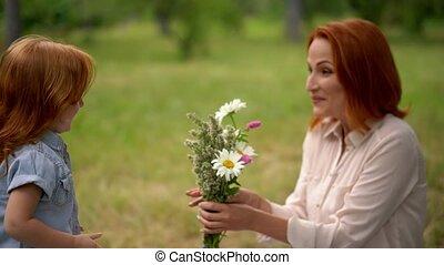 beau, gosse, mère, sourire, fleurs, donne