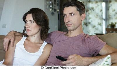 beau, gros plan, délassant, regardant télé, couple, divan, embrasser, maison